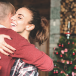 Young couple hugging in front of a Christmas tree, she