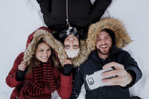 High angle friends taking selfie while lying at snow covered field