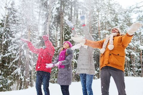 group of smiling men and women in winter forest