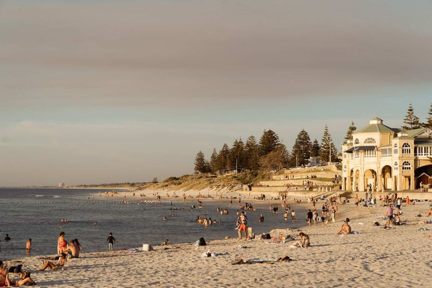 A wide shot showing a crowded Cottesloe Beach in Perth and the Indiana Tearooms.