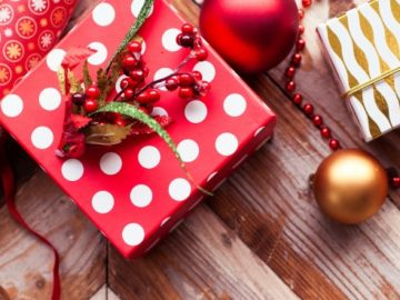 Rolls of Christmas wrap, ornament and small present in red and white paper.